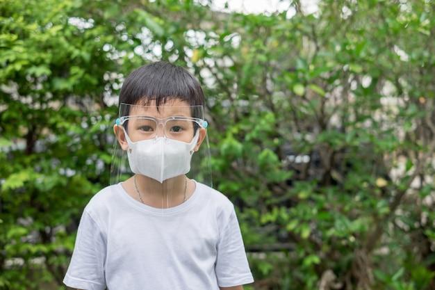 Aziatische leuke jongen die gezichtsschild en masker draagt