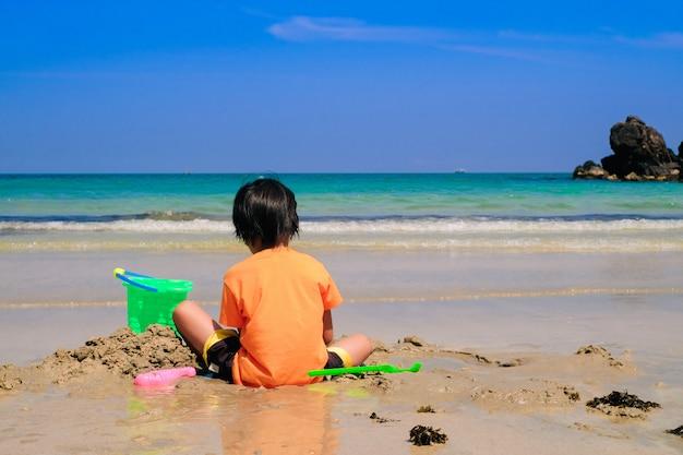 Aziatische leuke jongen die het zand alleen op het strand speelt.