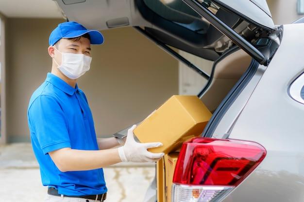 Aziatische levering man diensten koerier werken met kartonnen dozen op busje