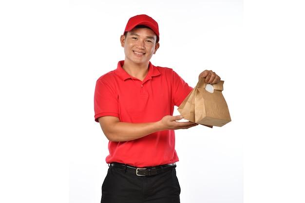 Aziatische levering man in rood uniform draagtassen van eten en drinken in handen geïsoleerd op een witte achtergrond