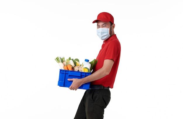 Aziatische leveringsmens die gezichtsmasker in de rode eenvormige mand van het holdings verse voedsel draagt die over witte achtergrond wordt geïsoleerd. koeriersdienst tijdens covid19.