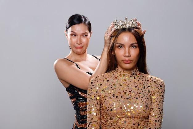 Aziatische lgbtgia + transgender vrouw zet diamond crown op nieuwe queen of night, miss beauty pageant queen contest slijtage cabaret pailletten sparkle pak jurk over grijze achtergrond geïsoleerd