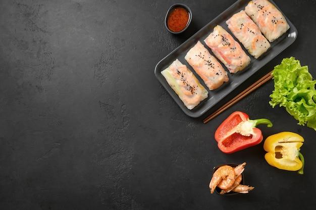 Aziatische loempia's met kleurrijke groenten, garnalen verpakt in rijstpapier op zwarte achtergrond met kopie ruimte. uitzicht van boven.