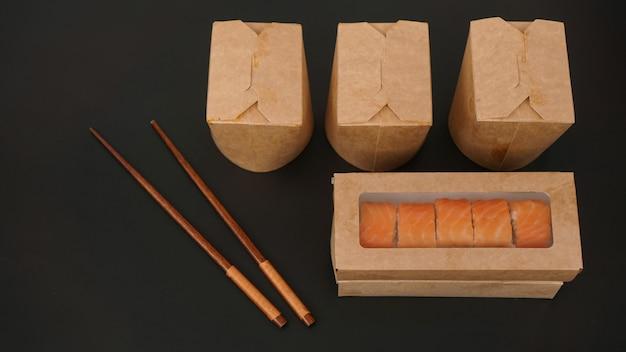 Aziatische maaltijdbezorging. verpakkingen voor sushi en woks. voedsel in papieren containers op zwarte achtergrond. open verpakking met zalmrolletjes