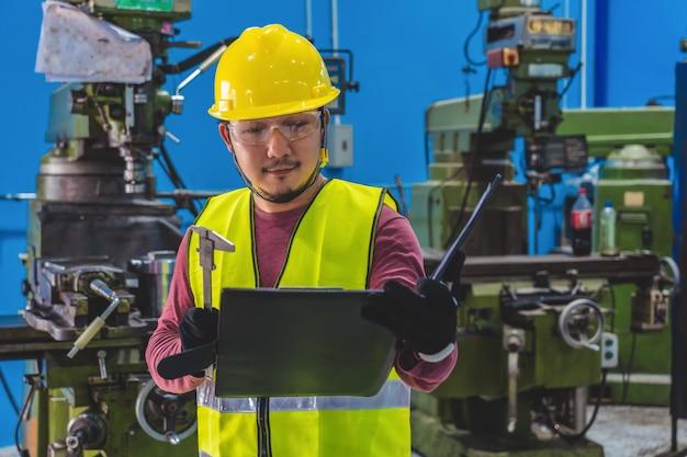 Aziatische machinist in veiligheidskleding die de takenlijst met specificatieblad controleren