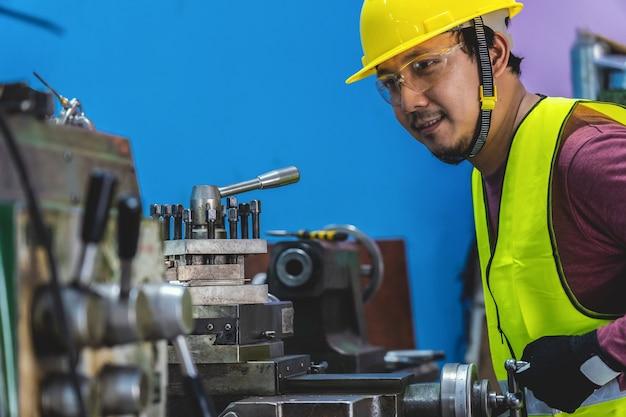 Aziatische machinist in veiligheidskostuum die de professionele draaibanken in metaalbewerkende fabriek in werking stellen
