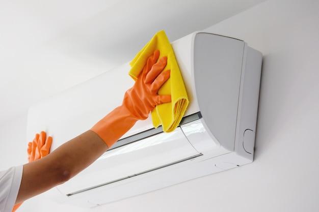 Aziatische man airconditioner schoonmaken met microvezeldoek