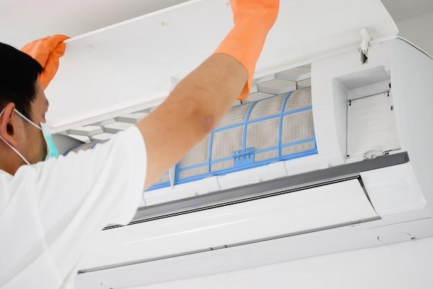 Aziatische man airconditioner vuil filter schoonmaken