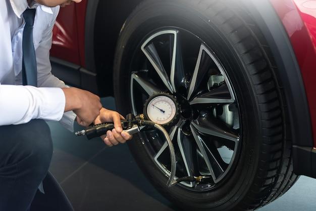 Aziatische man auto inspectie holdind tablet voor meten hoeveelheid opgeblazen rubber banden auto. close-up hand houden machine opgeblazen manometer voor auto bandenspanningsmeting voor auto