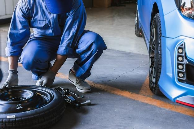 Aziatische man auto inspectie meet hoeveelheid opgeblazen rubber banden auto. close-up hand houden