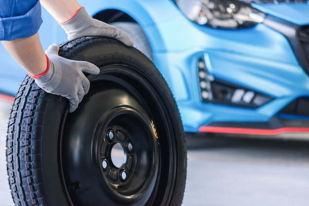 Aziatische man auto-inspectie meet hoeveelheid opgeblazen rubberen banden auto. close-up hand met band en blauwe auto voor bandenspanning meting voor auto, auto auto-industrie afbeelding