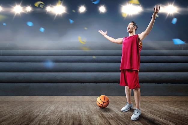 Aziatische man basketbalspeler viert de overwinning