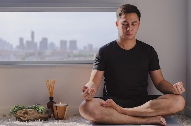 Aziatische man beoefenen van meditatie thuis zittend op de vloer.