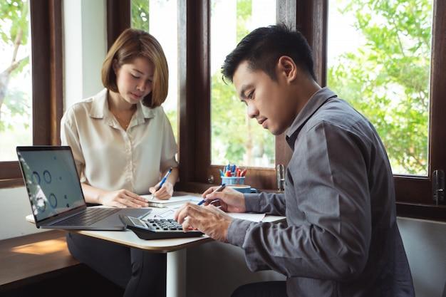 Aziatische man berekent bedrijfskosten met partner