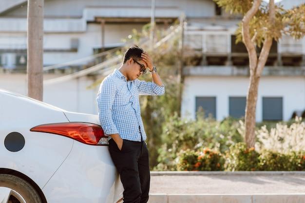 Aziatische man bezorgd en stress na een kapotte auto. kapotte auto op de weg. hulpdienst heeft auto kapot.