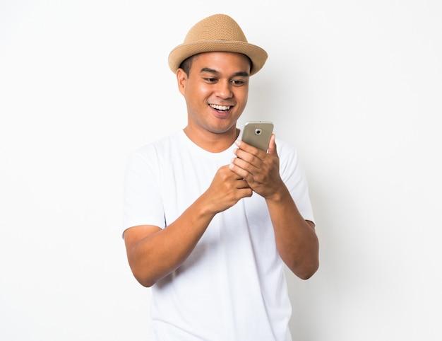 Aziatische man blij met zijn telefoon op witte muur