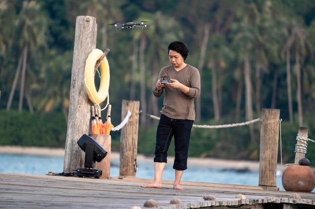 Aziatische man concentreert zich op het besturen en bewaken van de drone op de zeesteiger.