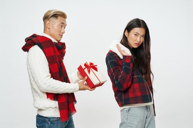Aziatische man die een vrouw een geschenk geeft, maar zij wijst het af. onbeantwoorde liefde concept