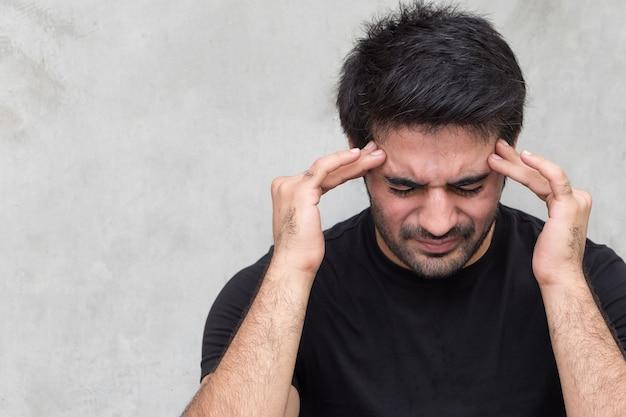 Aziatische man die lijdt aan hoofdpijn, duizeligheid, kater, migraine, stress