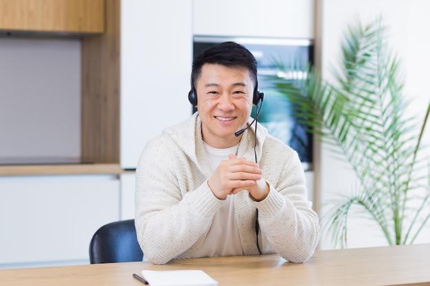 Aziatische man die online praat tijdens een videogesprek in de thuiskamer met headset