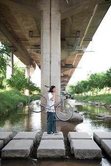 Aziatische man die zijn fiets vasthoudt