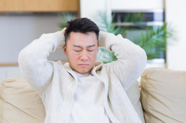 Aziatische man die zijn hoofd vasthoudt met ernstige hoofdpijn thuis in een kamer op de bank