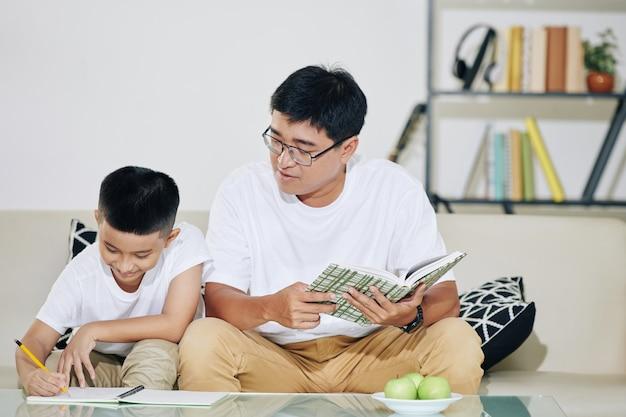 Aziatische man die zijn preteen zoon beheert die vergelijkingen oplossen bij het doen van huiswerk