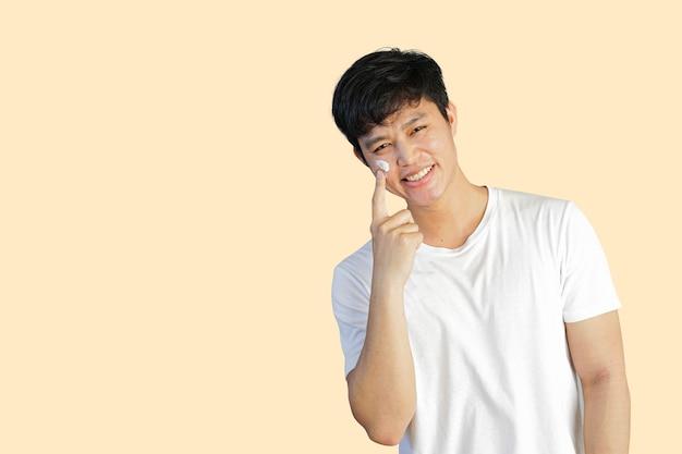 Aziatische man die zonnebrandcrème uvprotection toepast op het gezicht geïsoleerd op de achtergrond