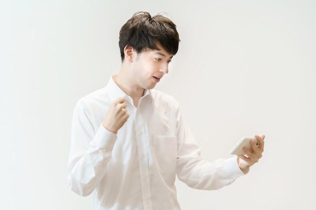 Aziatische man doet een lef pose terwijl hij naar het scherm van een smartphone kijkt