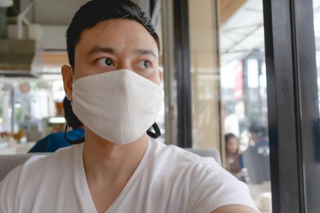Aziatische man draagt een wit masker ter bescherming van het covid-virus in een openbaar café.