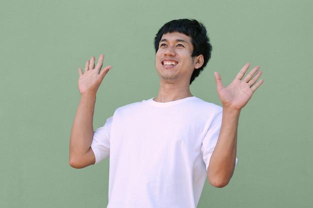 Aziatische man draagt een witte t-shirt glimlach op zoek naar bovenaanzicht met een blij gezicht. geïsoleerd uitknippadbeeld. afbeelding voor promotie en presentatie.