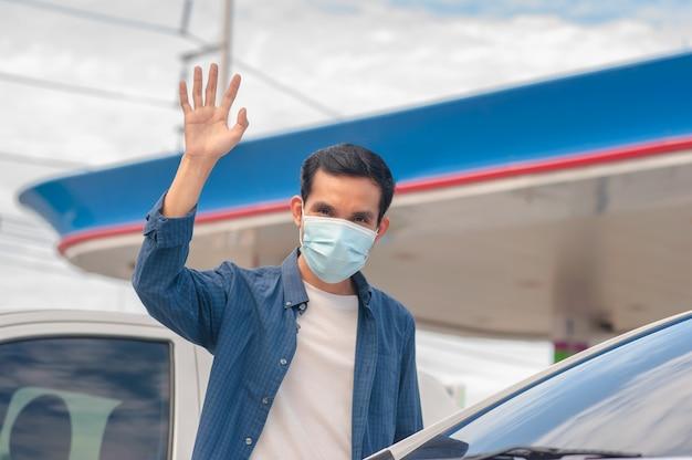 Aziatische man draagt gezichtsmasker en zegt hallo houd sociale afstand, voorkom coronavirus covid19