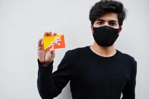 Aziatische man draagt helemaal zwart met gezichtsmasker houdt bhutan vlag in de hand geïsoleerd op wit. coronavirus land concept.