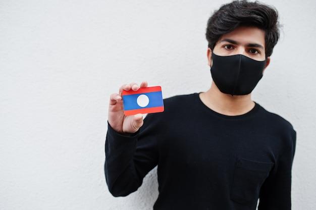 Aziatische man draagt helemaal zwart met gezichtsmasker houdt de vlag van laos in de hand geïsoleerd op wit. coronavirus land concept.