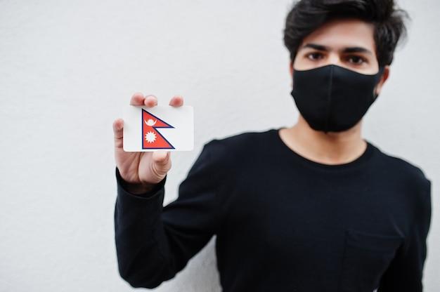 Aziatische man draagt helemaal zwart met gezichtsmasker houdt de vlag van nepal in de hand geïsoleerd op wit. coronavirus land concept.