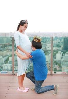 Aziatische man draagt kroon en knielen met het kussen van de buik van de zwangere vrouw op het dak van buil