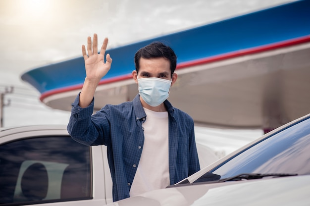 Aziatische man een dragen gezichtsmasker zegt hallo nieuwe normale sociale afstand nemen