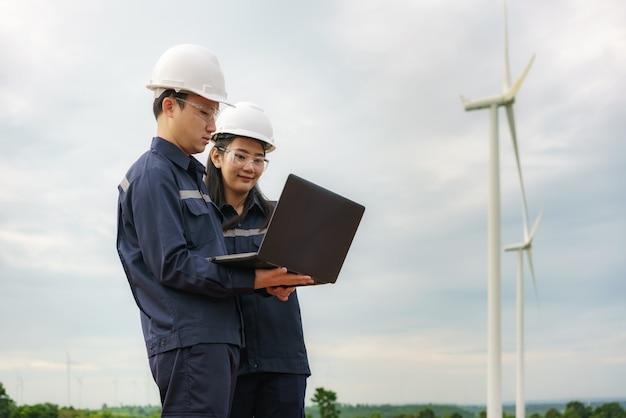Aziatische man en vrouw inspectie-ingenieurs voorbereiden en voortgangscontrole met laptop van een windturbine met veiligheid in windpark in thailand.