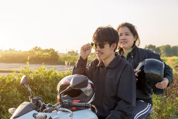 Aziatische man en vrouw met helm en dragen en vastmaken voordat grote fiets motorfiets rijden op de weg voor de veiligheid
