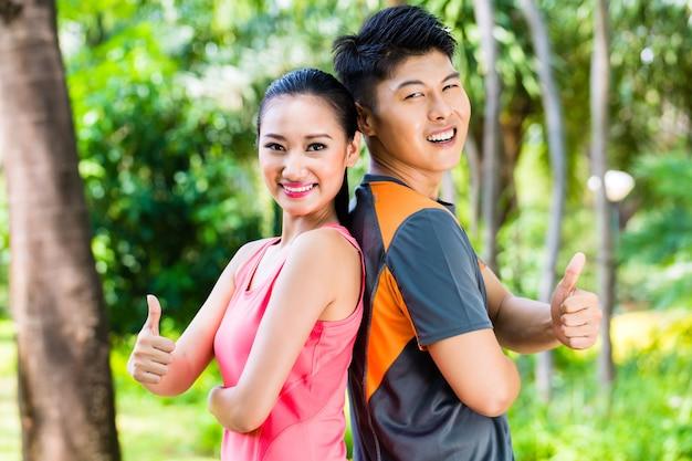 Aziatische man en vrouw nemen een pauze na fitness joggen in stadspark