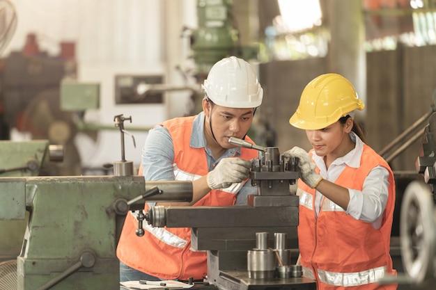 Aziatische man en vrouwenarbeidersfabriek die bij staal zware machine werken.