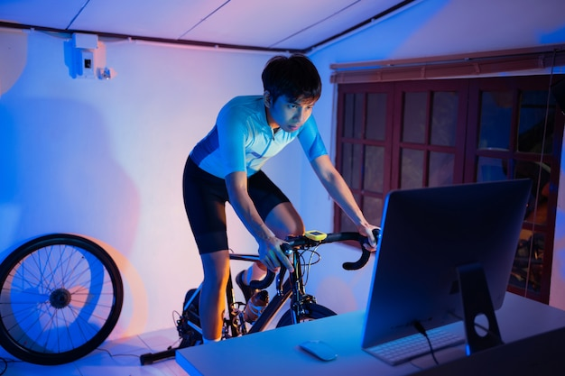 Aziatische man fietsen op de machine trainer die hij 's nachts thuis oefent. hij speelt online fietsspel