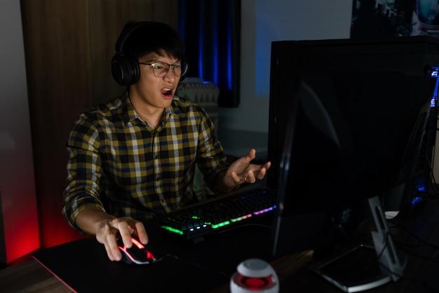 Aziatische man gamer in koptelefoon gestrest met hand voelt zich depressief of boos geschokt wanneer hij het videospel op de computer verliest angst en boos om een fout