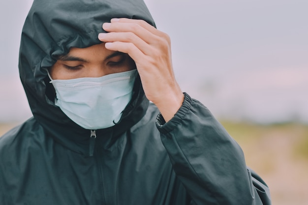 Aziatische man gebruikt chirurgisch masker of gezichtsmasker om coronavirus 2019 of covid 19 in het openbaar te beschermen