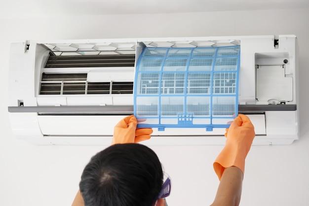 Aziatische man hand houden airconditioner filter reinigingsconcept