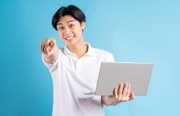 Aziatische man hield zijn laptop vast en wees met zijn hand