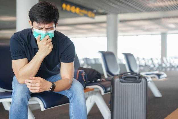 Aziatische man hoest in gezichtsmasker en zit in de poort van de luchthaven