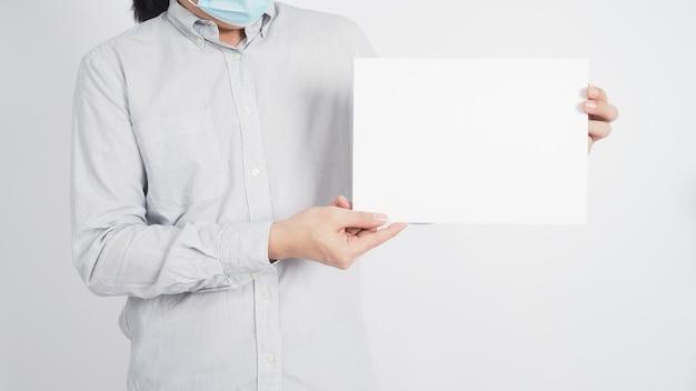 Aziatische man houdt een leeg wit bord vast en draagt een shirt op een witte achtergrond.