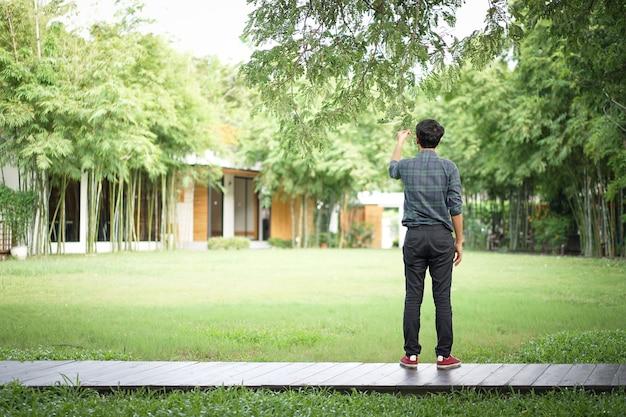 Aziatische man houdt het blad en de tak van een grote boom vast in een ontspannend gevoel op een houten loopbrug met een wazige tuin erachter. Premium Foto