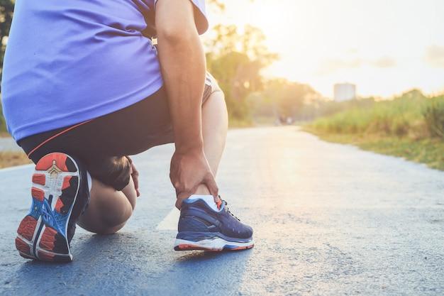 Aziatische man houdt op zijn enkel tijdens het hardlopen op weg in het park